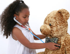 Girl giving teddy bear check up